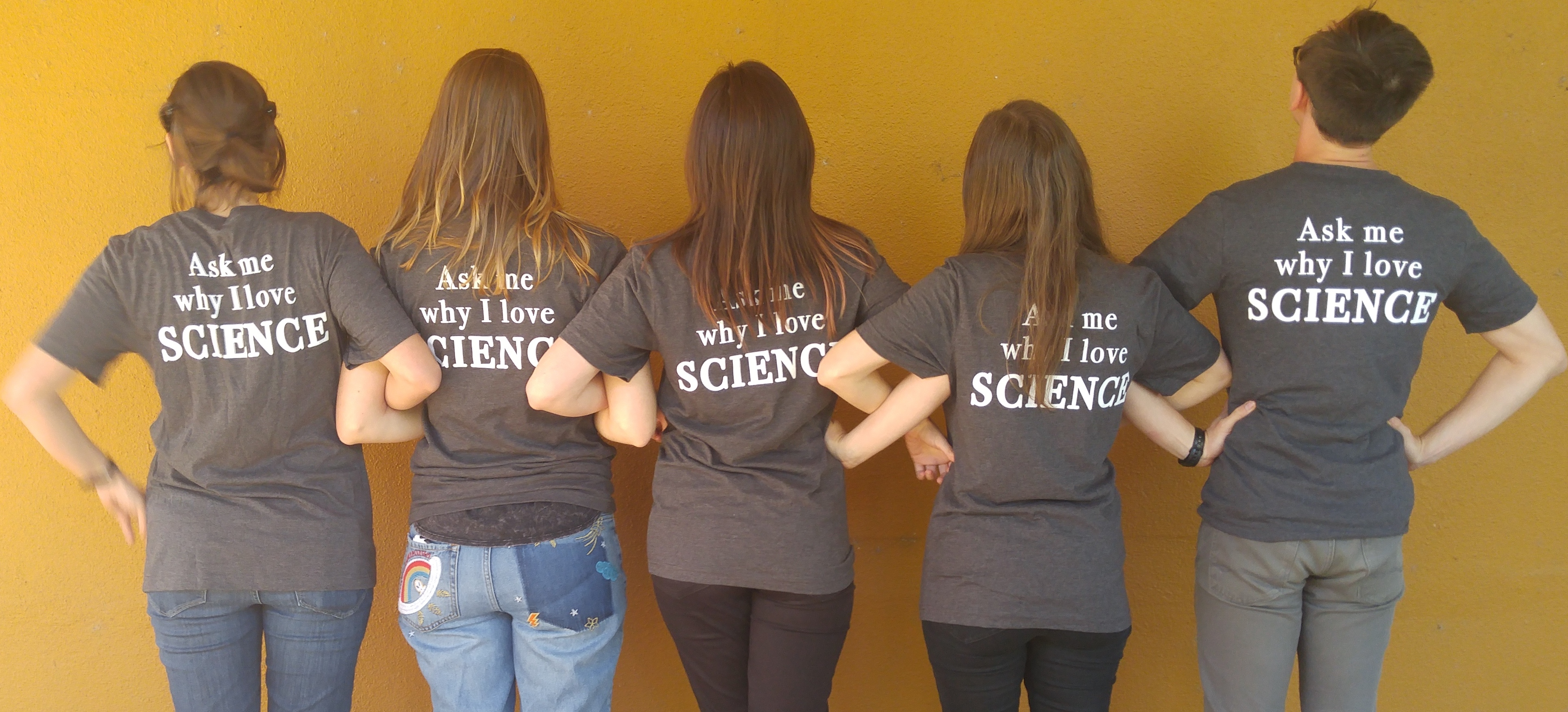 "People with linked arms showing back of T-Shirt, which says ""Ask Me Why I Love Science"""
