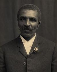 Black-and-white photograph of George Washington Carver. He is wearing a suit with a flower in the lapel.