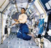Dr. Mae Jemison is floating in a corridor of a space craft.