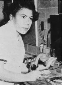Black-and-white photograph of Dr. Margaret Strickland Collins. She is wearing a light colored blouse and is sitting in front of a microscope.