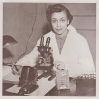 Sepia photograph of Dr. Jewel Plummer-Cobb. She is looking at the camera, sitting in front of a microscope.